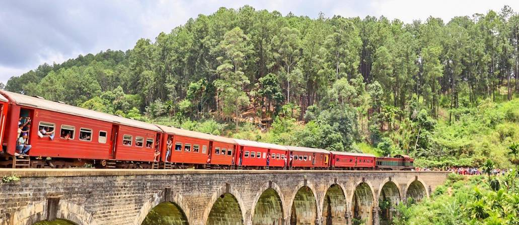 Red train going over Ella's Nine Arch Bridge